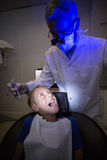 Dentist examining a young patient with tools. At dental clinic Stock Photography