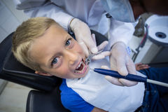 Dentist examining a young patient with tools. At dental clinic Stock Images