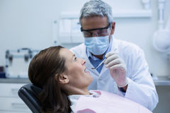 Dentist examining a young patient with tools. In dental clinic Royalty Free Stock Photos