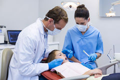 Dentist examining a young patient with tools. In dental clinic Royalty Free Stock Image