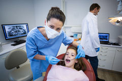 Dentist examining a young patient with tools. In dental clinic Royalty Free Stock Images