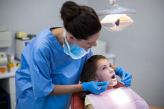 Dentist examining a young patient with tools. In dental clinic Stock Photo