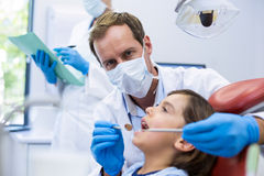 Dentist examining a young patient with tools Stock Images