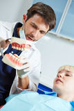 Dentist explaing denture to patient Royalty Free Stock Photos