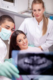 Dentist explaining the details of x-ray picture to his patient Royalty Free Stock Photos
