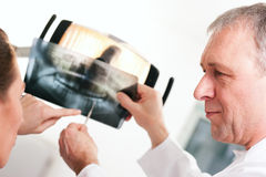 Dentist explaining x-ray to patient Stock Photography