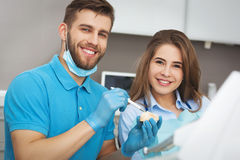 Dentist explaining to female patient how to brush her teeth. Royalty Free Stock Images