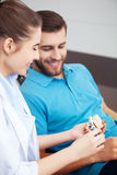 Dentist explaining to male patient how to brush his teeth. Royalty Free Stock Photos
