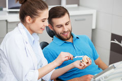 Dentist explaining to male patient how to brush his teeth. Stock Images