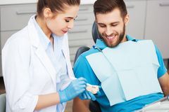 Dentist explaining to male patient how to brush his teeth. Stock Image