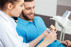 Dentist explaining to male patient how to brush his teeth. Stock Photos