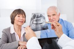 Dentist explaining x-ray to senior couple Stock Photos