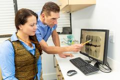 Dentist explains patient both looking at x-rays royalty free stock photography