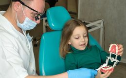 Little girl in dental clinic. Dentist explains rules of brushing the teeth of little girl holding toothbrush. Girl holding mock jaw. Lesson of oral hygiene stock photography