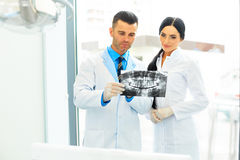 Dentist and female assistant are discussing dental X Ray image.  Stock Photos