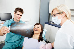 Dentist With Female Assistant Showing X-Ray Image Royalty Free Stock Images