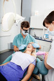 Dentist And Female Assistant Treating A Patient At Royalty Free Stock Image