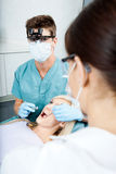Dentist And Female Assistant Treating A Patient At Stock Photo