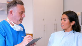 Dentist filling out dental records stock video