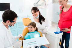 Dentist giving dental treatment to child and mother Royalty Free Stock Image