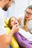 Dentist giving girl treatment Stock Images