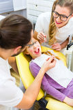 Dentist giving girl treatment  in dental surgery Royalty Free Stock Images