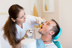 Dentist giving an injection of anesthesia to the patient Royalty Free Stock Photos