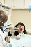 Dentist giving oral exam. Vertical, color image of an african american dentist working on a patient stock images