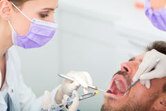 Dentist giving treatment - anesthetization syringe Stock Photo