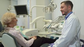 Dentist greets female client at his office. Middle aged handsome dentist greeting his female client at his office. Brunette bearded doctor shaking hands with Royalty Free Stock Image