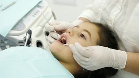 Dentist examining a teeth of little girl. Close-up. Dentist hands examining a teeth of little girl. Dentist using a mirror and dental proba Royalty Free Stock Image