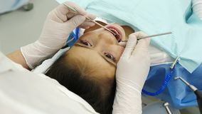 Dentist examining a teeth of little girl. Dentist hands take from table a dental proba and examining a teeth of little girl. Dentist using a mirror and dental Royalty Free Stock Photo