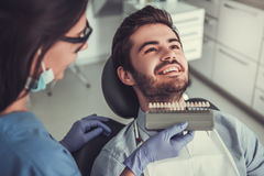 At the dentist. Handsome young men is sitting in dentist`s chair while doctor is examining his teeth Stock Image