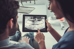 At the dentist. Handsome young patient and beautiful female dentist are looking at teeth image on a digital tablet Royalty Free Stock Photography
