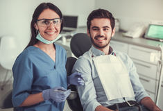 At the dentist. Handsome young patient is sitting in chair and smiling while visiting a beautiful female dentist Stock Photos