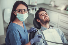At the dentist. Handsome young patient is sitting in chair and smiling while visiting a beautiful female dentist Stock Photo