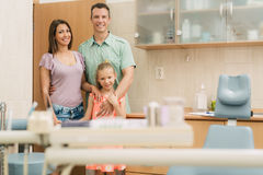 At The Dentist. Happy young family at visit in the dentist office. They are standing and looking at camera Royalty Free Stock Image
