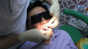Dentist is healing client teeth with mouth mirror. stock video footage