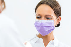 Dentist in her practice giving dental treatment. Dentist in her practice or office treating male patient with assistant wearing mask Stock Photography