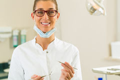 Dentist in her surgery hold mirror and scraper Royalty Free Stock Image