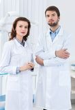 Dentist and his assistant. Wait the patient, white background Stock Photos