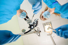 Dentist and his assistant in a dental clinic. Doctor looking through the microscope and holding dental probe and mirror. First-person view from below. Focus on Royalty Free Stock Photography