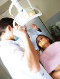 Dentist and his assistant examine a patient Stock Images