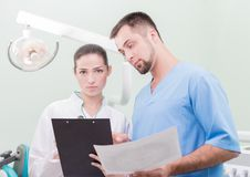Dentist and his assistant with papers Stock Photography