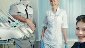 Dentist with his assistant stand near happy patient in special chair. stock footage