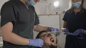 The dentist and his assistant use face bow while treating the patient`s teeth. Placement of the upper jaw relative to the stock video