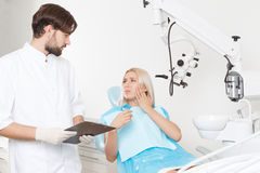 Dentist and his female patient in clinic Royalty Free Stock Photography