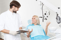 Dentist and his female patient in clinic. Sweet conversation. Young handsome smiling dentist with beard standing next to his female patient in armchair Stock Images