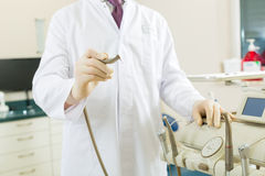 Dentist in his surgery, he holds a drill Stock Photography