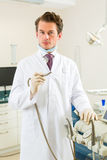 Dentist in his surgery, he holds a drill Stock Images